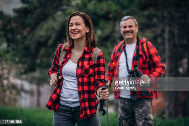 father and adult daughter hiking and exploring - plaid shirt stock pictures, royalty-free photos & images