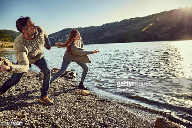 father and adult daughter skipping stones on a river - nur erwachsene stock-fotos und bilder