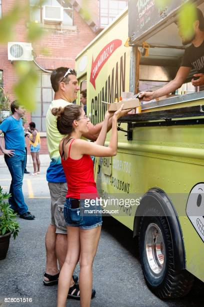 Father and adult daughter taking out lunch from food truck in city street.
