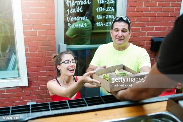 "father and adult daughter taking out lunch from food truck. - ""martine doucet"" or martinedoucet stock pictures, royalty-free photos & images"
