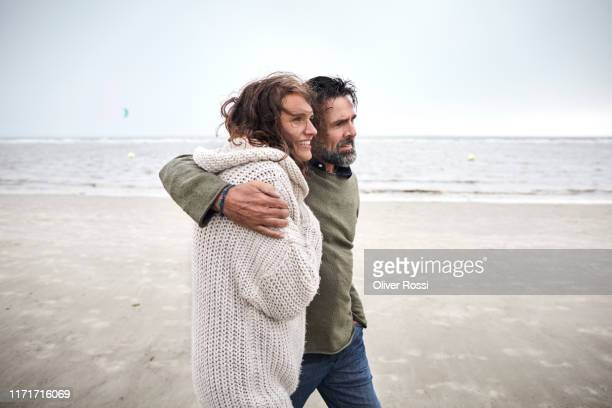 father and adult daughter walking on the beach - daughter stock pictures, royalty-free photos & images