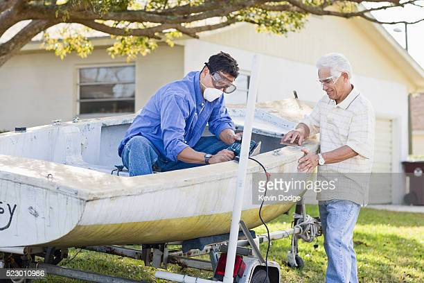 Father and adult son cleaning up old boat