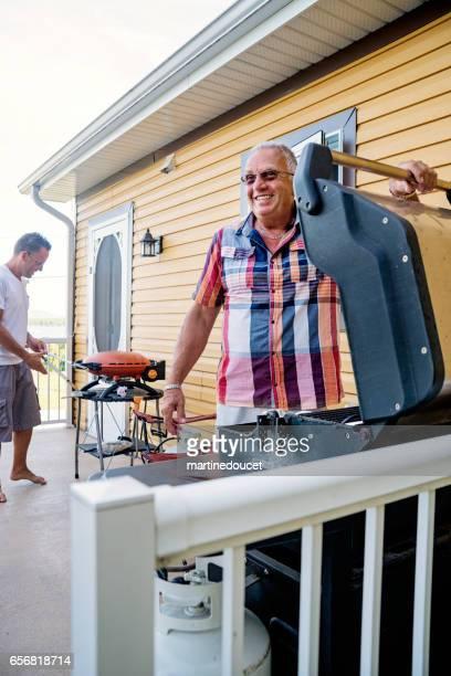 """far och vuxen son matlagning på sommaren familj barcecue. - """"martine doucet"""" or martinedoucet bildbanksfoton och bilder"""