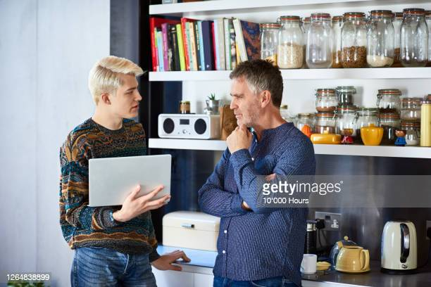 father and adult son discussing with laptop - adult stock pictures, royalty-free photos & images