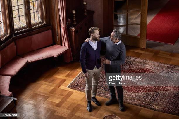 father and adult son in a villa talking - prosperity stockfoto's en -beelden
