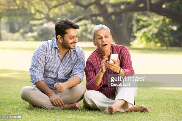 father and adult son relaxing in park stock photo - son stock pictures, royalty-free photos & images