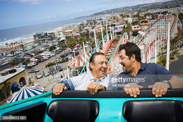 Father and adult son riding rollercoaster