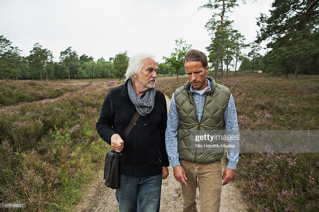 Father and adult son walking on dirt track : Stock Photo