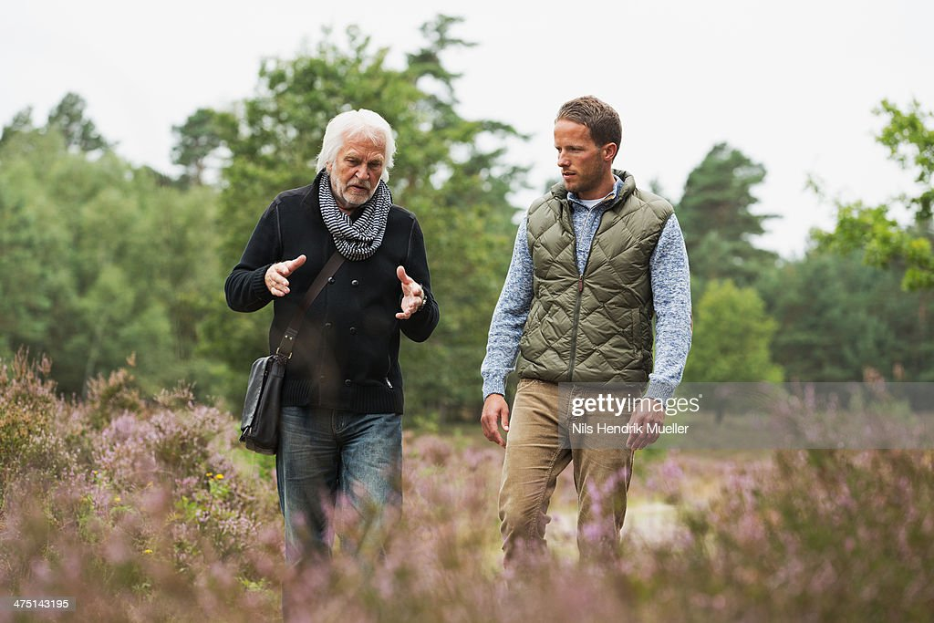 Father and adult son walking : Stock Photo