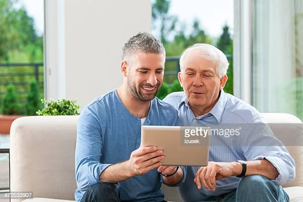 Pai e Adulto filho com tablet digital