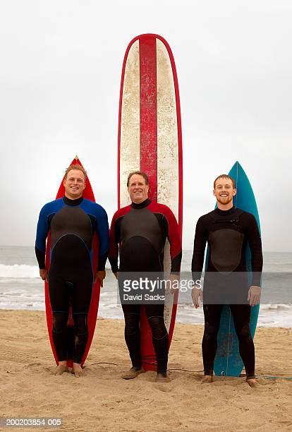 Father and adult sons with surfboard, portrait