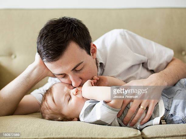 father and baby boy (6-11 months) lying on sofa - 6 11 months stock pictures, royalty-free photos & images