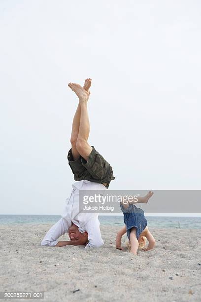 Father and baby boy (1-3) performing headstand on beach