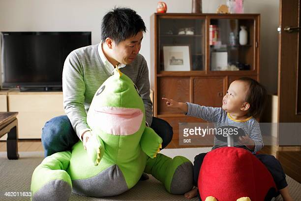 Father and baby boy playing stuffed toy