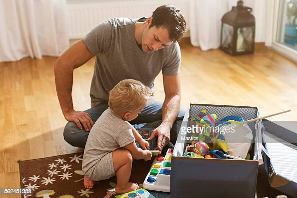 Father and baby boy playing toys on floor at home