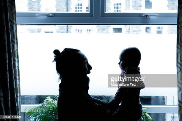 father and baby boy son looking each other in front of the window with back lit - genderblend stock pictures, royalty-free photos & images