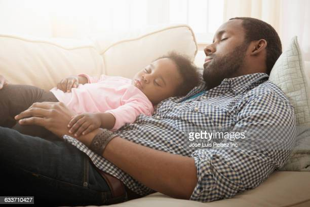 Father and baby daughter napping on sofa