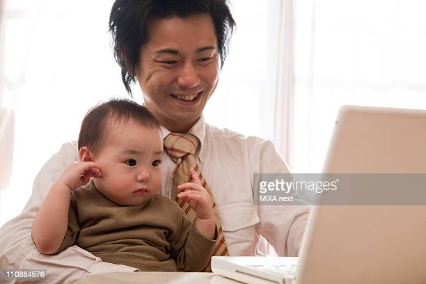 Father and Baby Girl Looking at PC