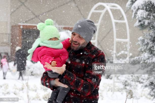 father and baby girl playing in the snow - winter coat stock pictures, royalty-free photos & images