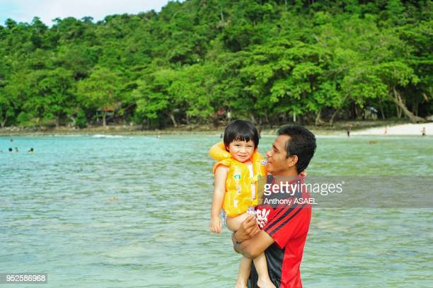 father and baby in the tropical beach Pulau Weh Banda Aceh Sumatra Indonesia
