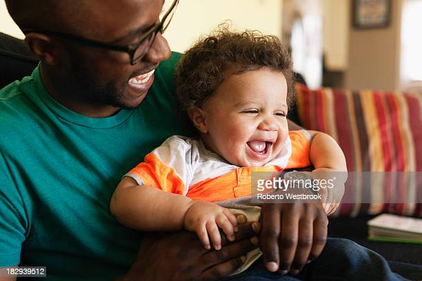 Father and baby laughing on sofa