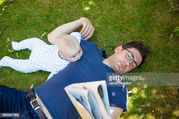 Father and baby lie on grass reading paper