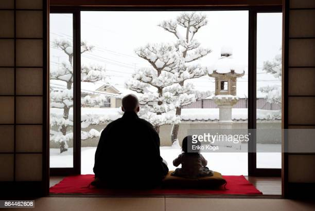 Father and baby looking at snowy garden