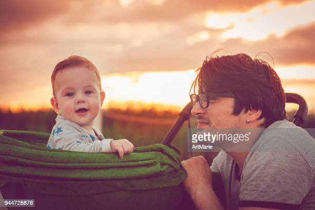 father and baby outdoors in sunset - pushchair stock pictures, royalty-free photos & images