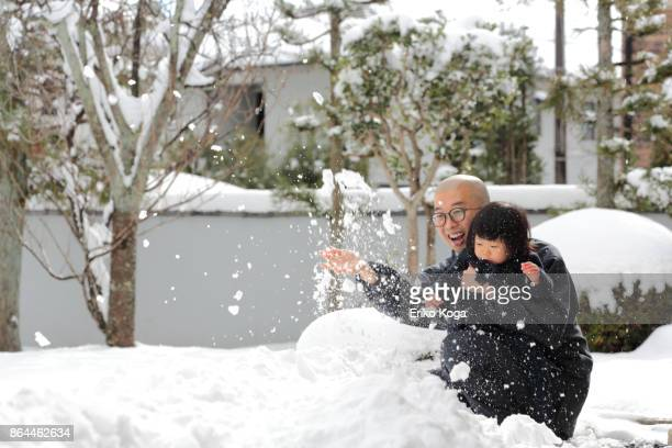 Father and baby playing with snow in snowy garden