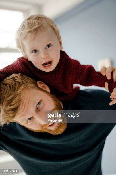 Father and baby son having fun together at home