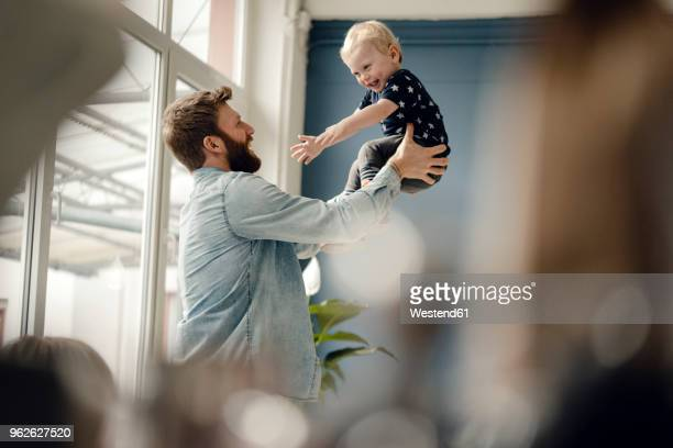 father and baby son having fun together at home - picking up stock pictures, royalty-free photos & images