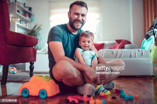 vader en zoontje plezier met speelgoed in de woonkamer - alleenstaande vader stockfoto's en -beelden