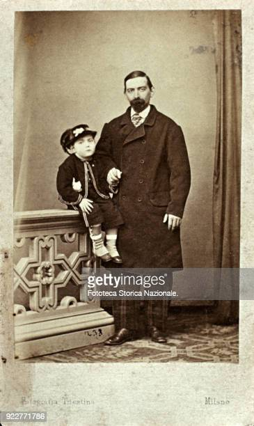 Father and baby son posing The man holds the child by the hand who has been wisely seated on the balustrade of the atelier to be closer to him in the...