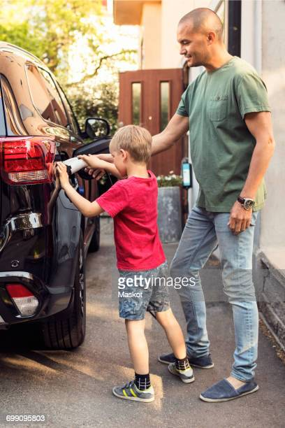 Father and boy charging electric car by house