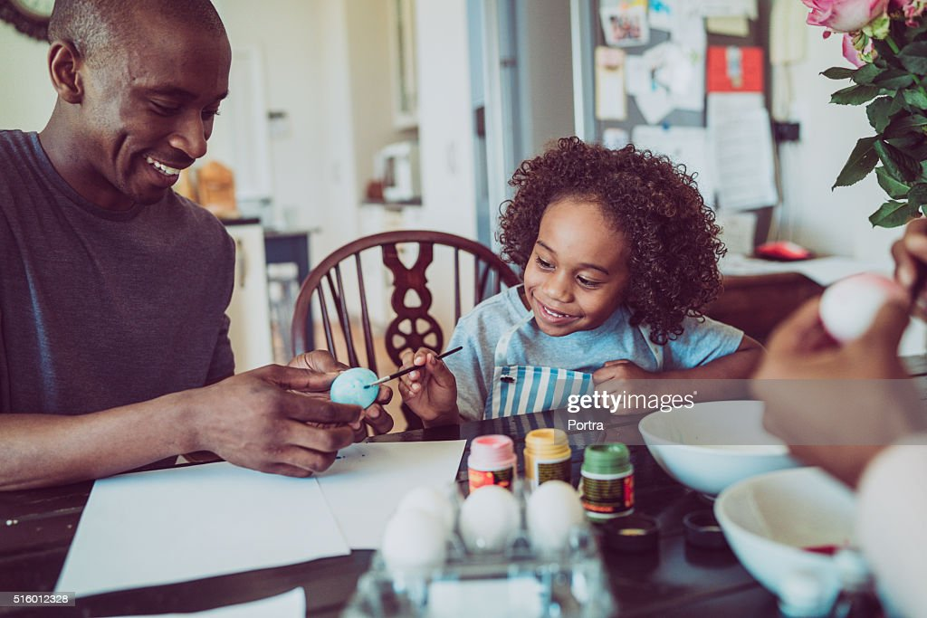 Father and boy colouring Easter egg together : Stock Photo