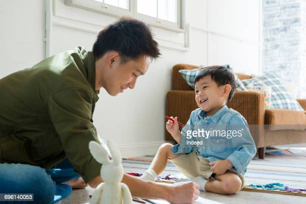 Father and boy drawing together on floor