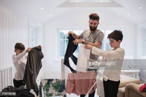 Father and boys drying clothes at home