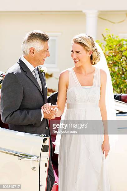 Father And Bride Holding Hands While Standing By Car