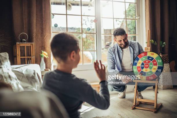 father and  chidlren playing  indoors at home - darts stock pictures, royalty-free photos & images
