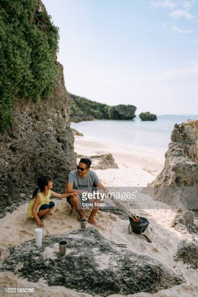 father and child enjoying beach campsite, okinawa, japan - ippei naoi stock pictures, royalty-free photos & images