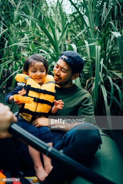 Father and child enjoying jungle river kayaking