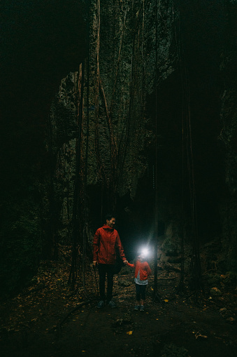 Father and child exploring dark cave with headlamp, Okinawa, Japan - gettyimageskorea