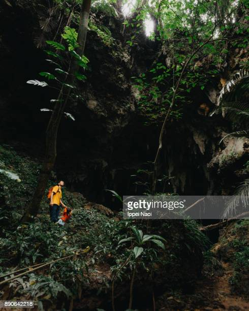 Father and child exploring jungle cave, Iriomote-jima, Japan