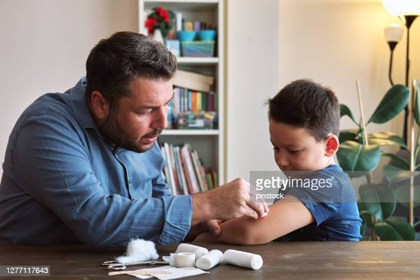 father and child first aid - first aid kit stock pictures, royalty-free photos & images