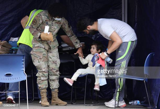 Father and child from Afghanistan walk together with a medical officer after their arrival to Ramstein Air Base on August 26, 2021 in...