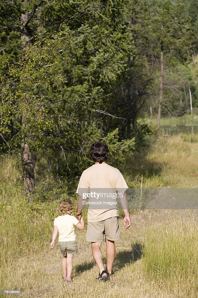 Father and child holding hands while walking : Foto de stock