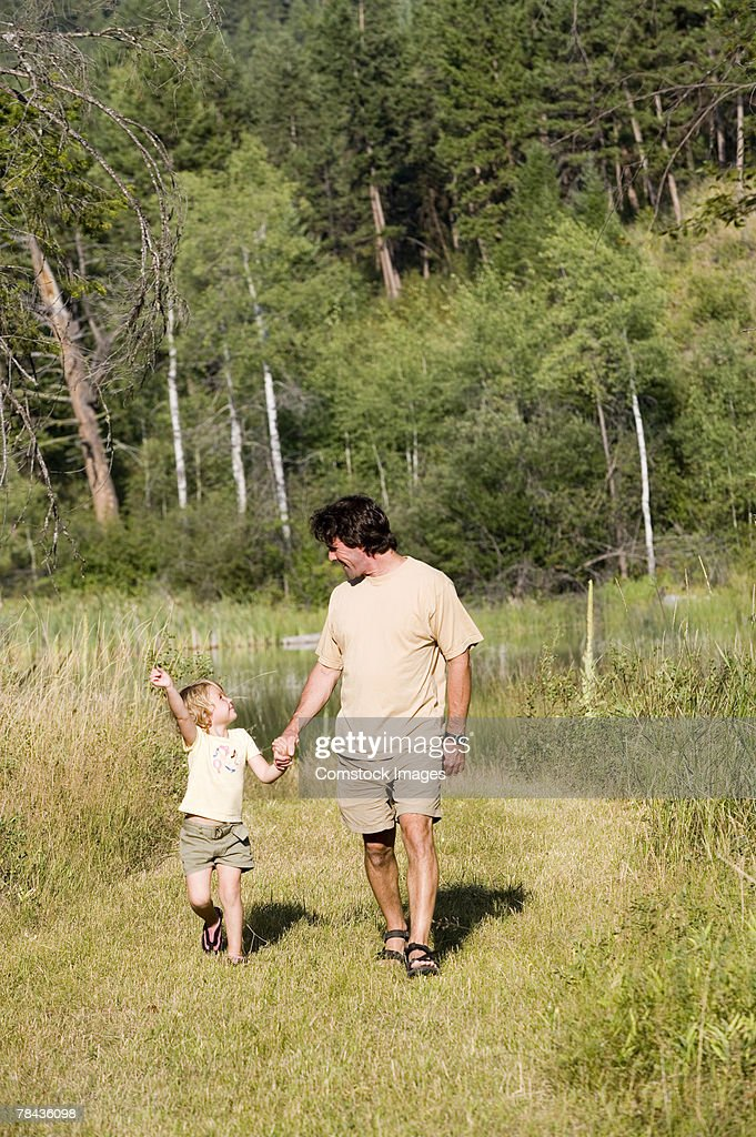 Father and child holding hands while walking : Stockfoto