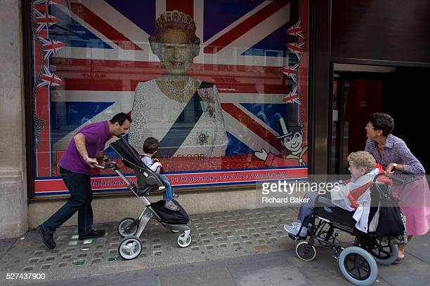 A father and child in a buggy and a daughter with her aged mother in a wheelchair admire a Lego representation of Queen Elizabeth ahead of a weekend...