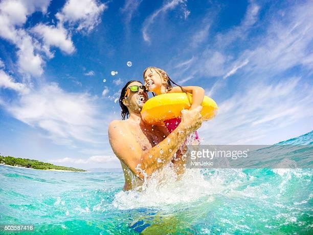 Vater und Kinder springen und Spaß miteinander in Meer