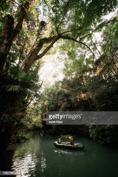 Father and child kayaking on river in rainforest, Japan